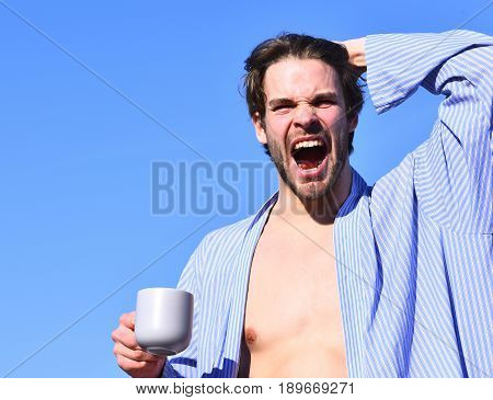 Caucasian Macho In Blue Striped Pajamas Holding Cup