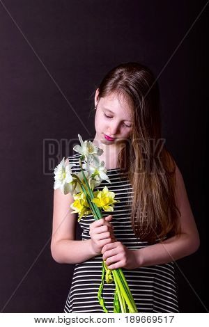 Girl holding a bouquet of daffodils. Portrait on a dark background. A vertical image. Girl in striped dress with her hair