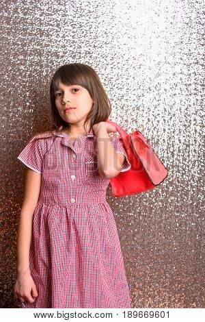 Small Pretty Girl With Fashionable Red Leather Bag On Silver