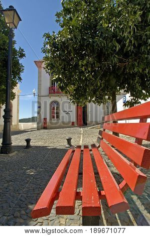 A striking red bench matches the red door of the traditional building behind it in Mertola village.