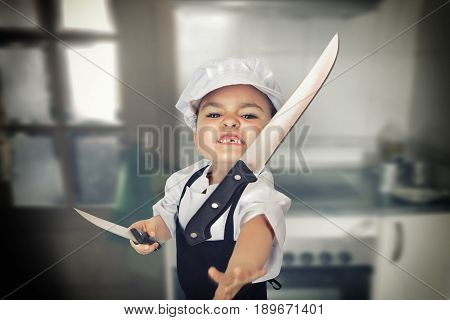 Funny portrait of a six years girl dressed as a cook throwing a knife