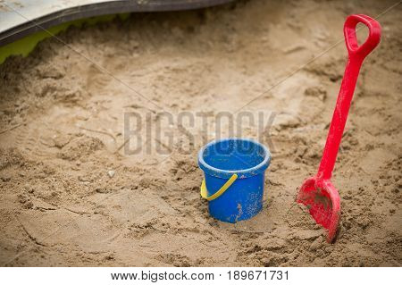 Children plastic shovel and pail in the sandbox. Baby's toys outdoor.