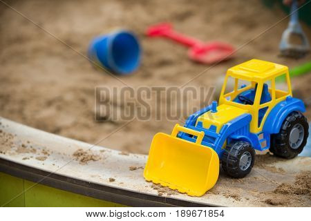 Closeup of bright blue and yellow tractor and children plastic shovel and pail in the sandbox. Baby's toys outdoor.