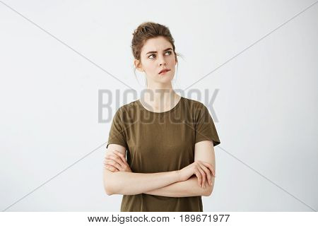 Beautiful shy young girl with hair bun thinking biting lip over white background. Crossed arms. Copy space.