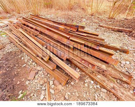 Heap of rusty rails in junkyard. Stock of steel rails from closed railway station. Metal material is waiting for transport to steel foundry for recycling