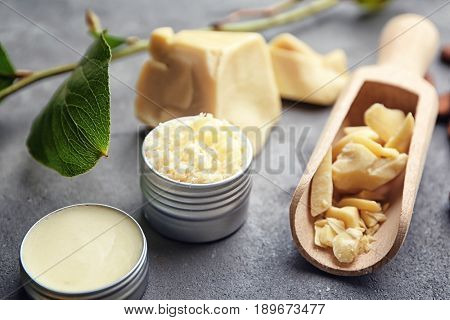 Jars with cocoa butter cosmetics and ingredients on table