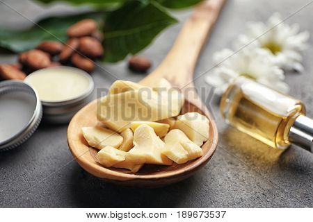 Wooden spoon with cocoa butter for lotion on table