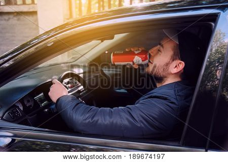 A man drinking beer while driving car