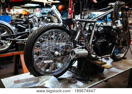 Background image of big disassembled motorcycle in workshop, ready for repair, tune up and customizing works