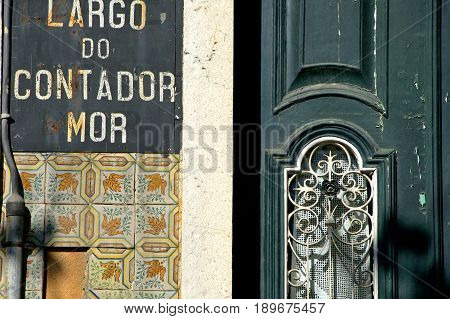 An old tradtional house with a weathered green door in Lisboa.
