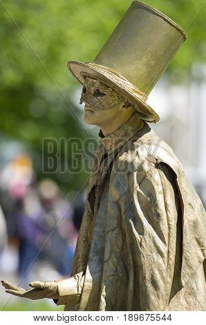 Saint Petersburg, Russia - June 4, 2017: VII international festival of street theatres `Elagin Park`. Living statue of a man in a cloak and top hat