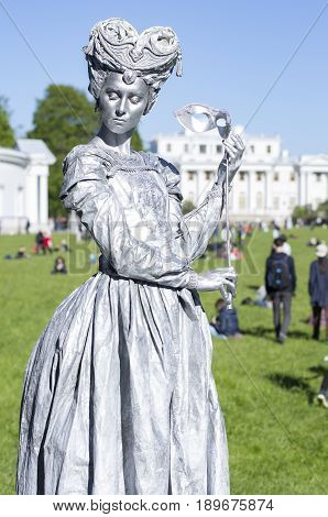 Saint Petersburg, Russia - June 4, 2017: VII international festival of street theatres `Elagin Park`. Living statue lady with the mask in hand against Palace
