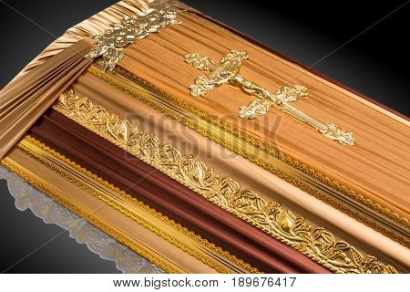 closed beige coffin covered with cloth isolated on gray background. coffin close-up with gold Church cross on royal background. Ritual objects for burial. Surrender body dust of the earth. Christian funeral ritual