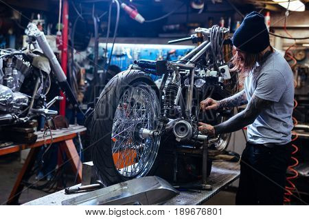 Side view portrait of tattooed man working in garage repairing motorcycle and customizing it