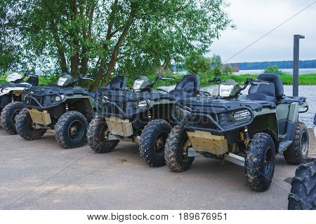Few parked quad bikes are waiting for their drivers. Entertainment for adults - race in rough terrain, mud and sand dunes. ATV rental.