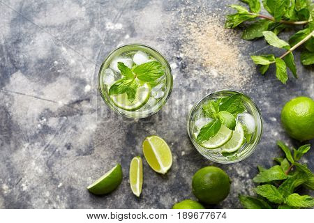 Mojito cocktail alcohol drink top view in highball glass, summer tropical vacation beverage with rum, mint leaves, lime citrus juice, soda water and ice on concrete table.