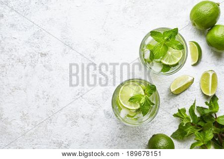 Mojito cocktail alcohol bar long drink traditional Cuba fresh tropical beverage top view copy space two highball glass, with rum, spearmint, lime juice, soda water and ice on white concrete table.