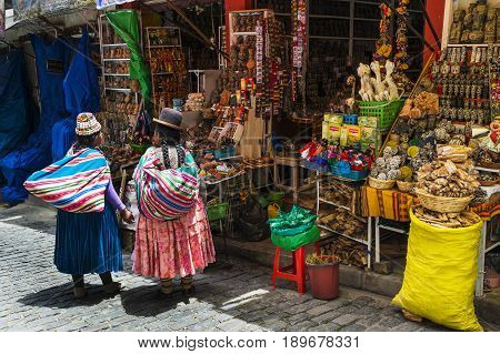 La Paz Bolivia - December 8 2013: Two local woman wearing traditional clothing in front of a store in a street of the city of La Paz in Bolivia