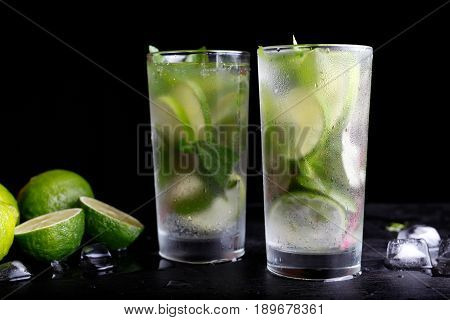 Mojito traditional summer vacation refreshing cocktail alcohol drink in highball glass, soda water beverage, lime juice, mint leaves, sugar, and rum. Dark black background with copy space text