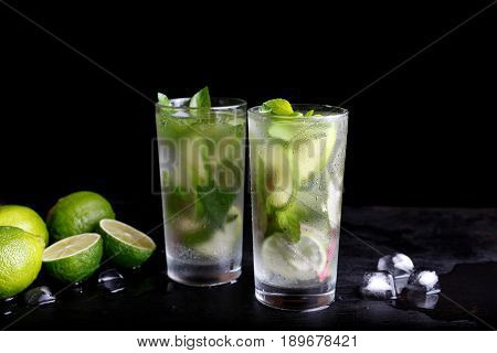 Mojito summer vacation refreshing tropical cocktail alcohol drink in highball glass, soda water beverage, lime juice, mint leaves, sugar, and rum. Dark black background with copy space text