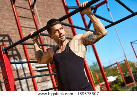 Man doing body builder exercise, pull-ups at outdoor gym