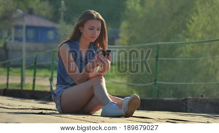 The girl is holding smartphone. Internet girl in smartphone social media sits on iron bridge outdoor