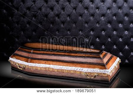 closed wooden brown coffin with cloth isolated on gray luxury background. casket with shadow on royal background. Ritual objects for burial. Surrender body dust of the earth. Christian funeral ritual