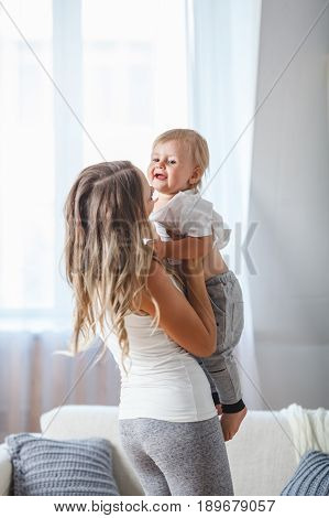 picture of happy mother holding adorable baby boy indoors