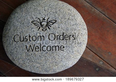 Large stone engraved with the words 'Custom orders welcome.'