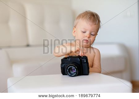 Baby boy with blue eyes indoor portrait. Toddler child exploring old camera