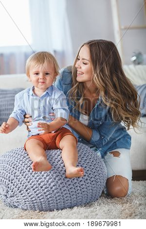 mother and son playing at home, boy sitting on the pouf
