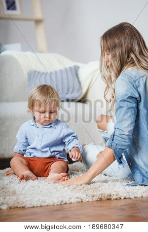 mother and son playing on the carpet near sofa, indoors