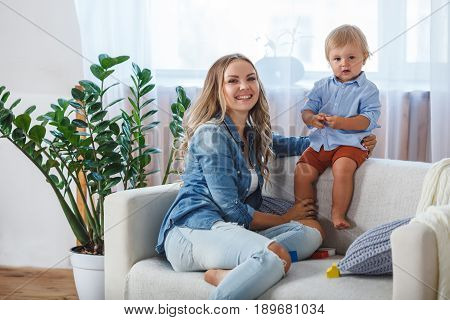 mother and son playing on sofa at home, they looking at camera