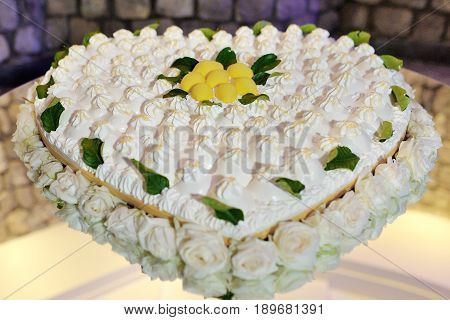 Beautiful heart shaped wedding lemon cake decorated with roses