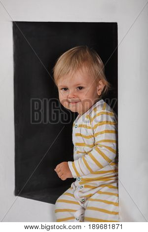 portrait of smiling cute little boy wearing sleepwear in the black wall niche