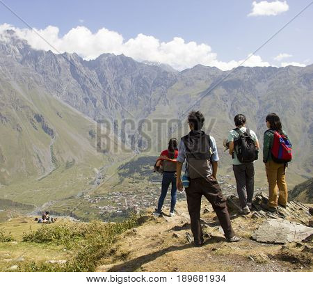 Young travelers with backpacks at their backs are admiring the high mountains. Georgia. The mountain Kazbek.