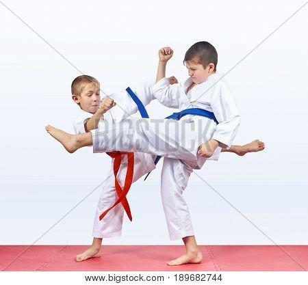 Karateka children beat kick leg on the mats