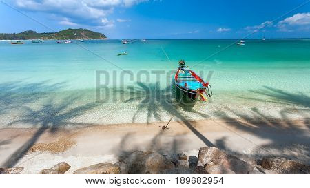 Sea and wooden boat in the morning. The shadow of the trees falls on the white sandy beach and turquoise water.