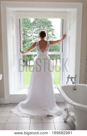 Bride Stood In The Bathroom Window Looking Outside