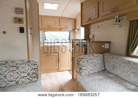 Inside A Caravan Showing Seats And Kitchen Area