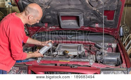 Mechanic working on a car engine he is holding a can or aerosol spray