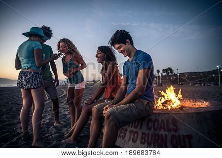 Multicultural group of friends partying on the beach - Young people celebrating during summer vacation summertime and holidays concepts
