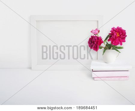 White blank wooden frame mockup with a peony flowers bouquet in a porcelain cup and pile of books lying on the table. Poster product design, styled stock feminine photography. Home decor.