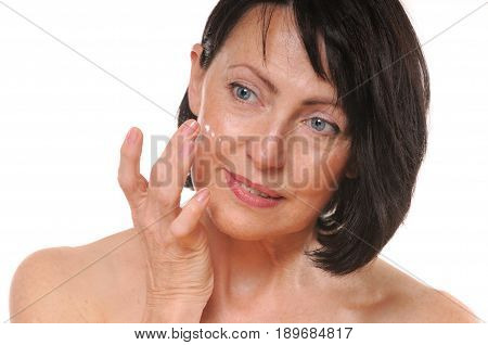 close up portrait of pretty senior woman using face cream, beauty and care concept