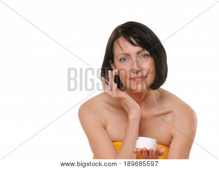 portrait of pretty senior woman using face cream, beauty and care concept