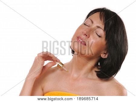 portrait of pretty senior woman using oil on her body, beauty and care concept