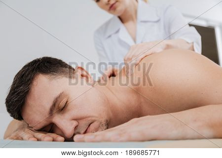 Caught in relaxation. Prominent capable local expert conducting a special therapeutic procedure and massaging mans back while assisting him getting rid of pain