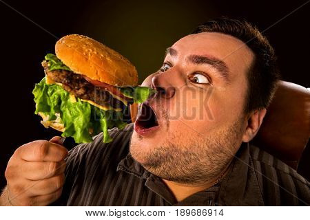 Diet failure of fat man eating fast food . Happy smile overweight person who crazy makes squint for fun eating huge hamburger on fork. Junk meal leads to obesity.