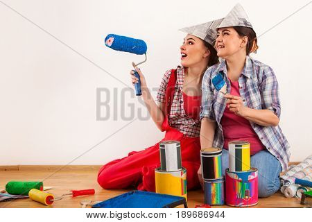 Repair home women holding bank with paint for wallpaper. Elderly mother and daughter renovation apartment on isolated. Home renovation. Tired workers sit on floor and rest from work done.