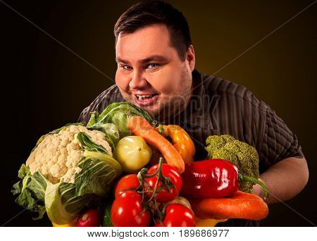 Diet fat man eating healthy food with vegetables cauliflower and sweet pepper with radish , tomatoes for overweight male. Male trying to lose weight first time .Hungry person ready to eat everything.